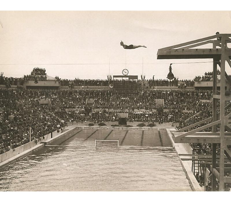"""Texte de la légende au verso : """"La première journée des championnats d'Europe de natation qui a eu lieu hier, au stade nautique des Tourelles, a remporté un énorme succès populaire et s'est déroulé devant une assistance record. Un beau plongeon de mme Creté-Flavier pendant l'épreuve féminine."""" 1931"""