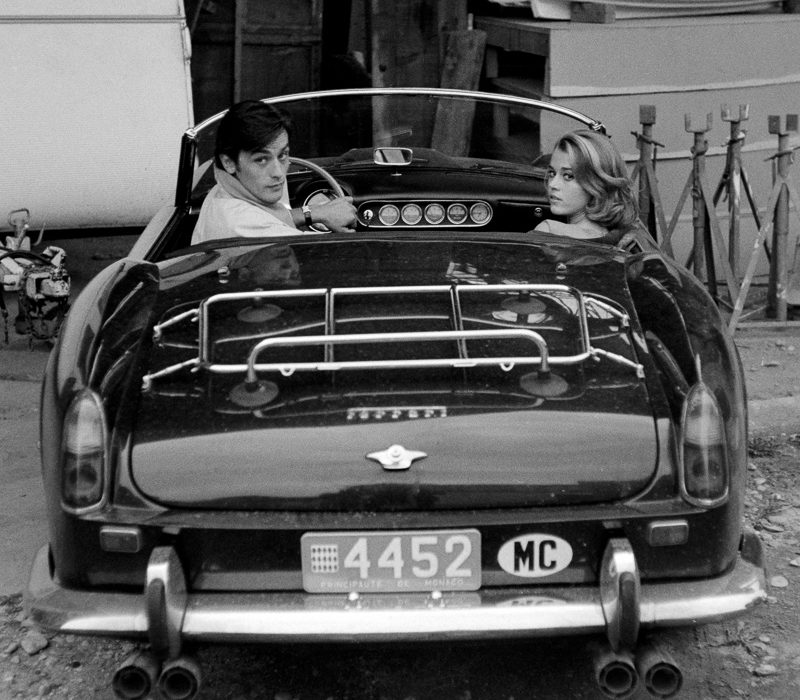 "Alain Delon and Jane Fonda arriving at the film set of ""Les Félins"" (""Love Cage""). Ferrari 250 GT Spider California 1961. Antibes 1964. This car of Alain Delon was hammered 2015 for a record-breaking $18.5 million at an auction at Artcurial in Paris. The 250 GT Spyder California, Chassis No 2935, had been bought new by the actor Gérard Blain, then sold to fellow actor Alain Delon, who was photographed several times at the wheel of this machine, including in 1964. One of 37 examples, this Pininfarina-designed cabriolet, its whereabouts unknown to marque historians until now, is bound to attract the attention of collectors of important historic Ferrari."